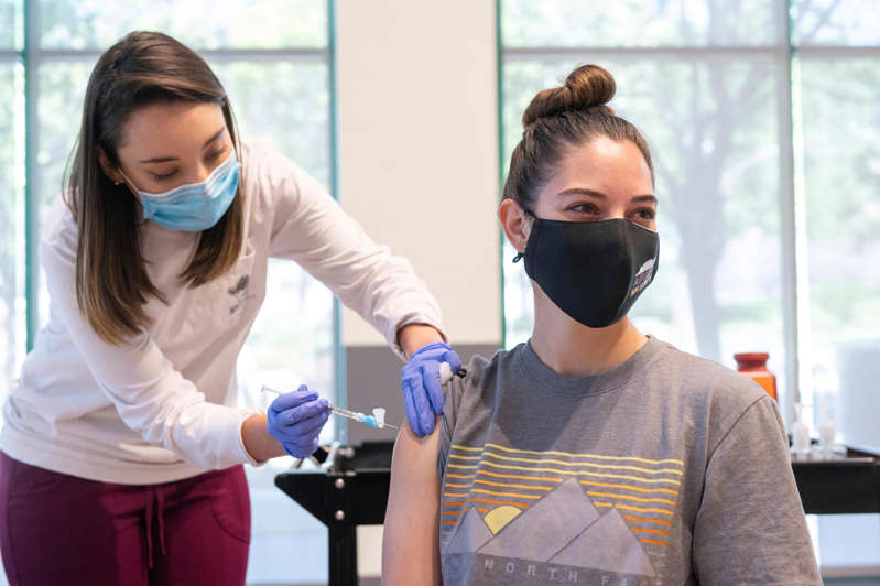 a man standing next to a window: This photo provided by New Mexico State University shows Aggie Health and Wellness Center nurse Marissa Archuleta (left) administering a Johnson & Johnson COVID-19 vaccine to Lauren Naranjo at a walk-in clinic at Corbett Center in Las Cruces, New Mexico.
