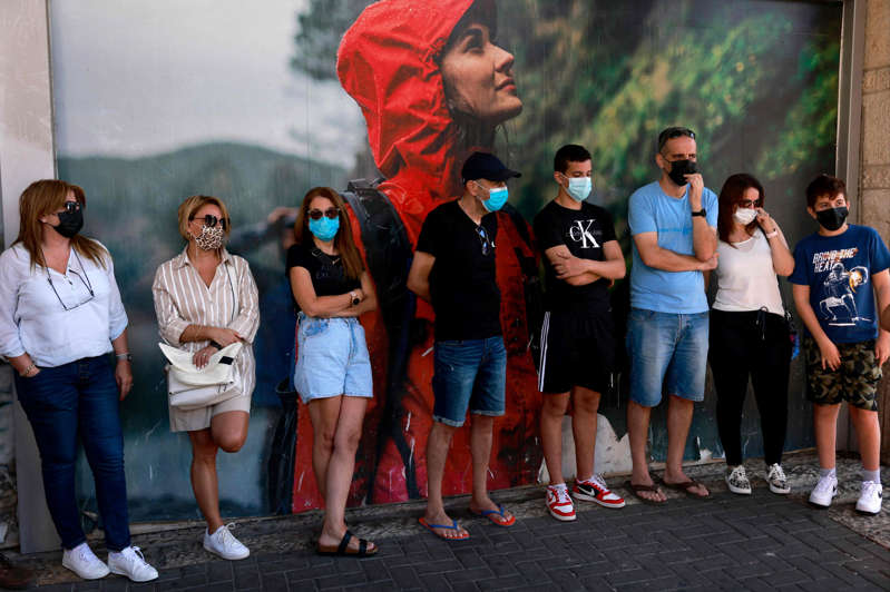 a group of people standing in front of a crowd posing for the camera:  (AFP via Getty Images)
