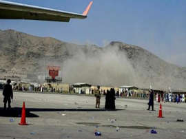 a group of people standing around a plane: Kabul Airport suicide attacker was freed by Taliban after four years in CIA custody for New Delhi terror plot