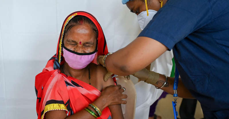 a little boy wearing a hat: A woman reacts as she gets inoculated with a dose of the Covishield vaccine against Covid-19 at a vaccination center in Mumbai on August 12, 2021.