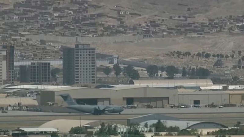 a plane sitting on top of a building: Military planes have been arriving, and leaving, in a steady stream at Kabul airport