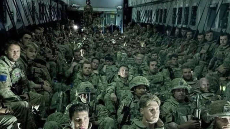 a group of people posing for the camera: Troops left Afghanistan on packed military flights