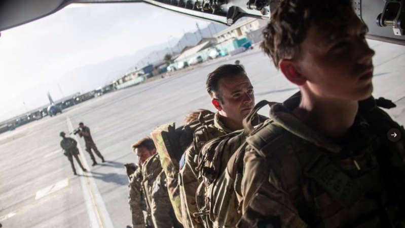 a man wearing a uniform: The final flight carrying UK troops left on Saturday evening. Pic: MoD