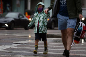 a man riding a skateboard down a street: Aban Korb, 4, walked with his father Geoff on his way to camp during early rain in Boston on August 19, 2021.