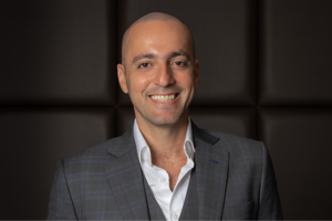 a man wearing a suit and tie smiling at the camera: Elie Milky, Vice President – Development for the Radisson Hotel Group in the Middle East, Cyprus, Greece, and Pakistan