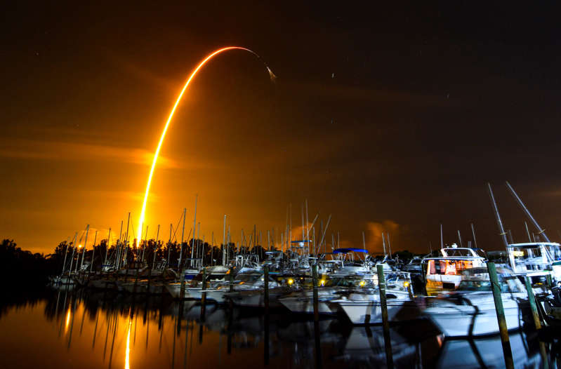 a boat is docked next to a body of water: Tthe launch of a SpaceX Falcon 9 rocket on a resupply mission for Nasa to the International Space Station from Pad 39A at Kennedy Space Centre, seen from Merritt Island, Florida (Malcolm Denemark/Florida Today via AP)