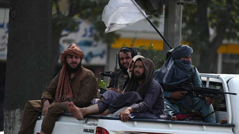 a group of people sitting around a car: Taliban militants patrol Kabul