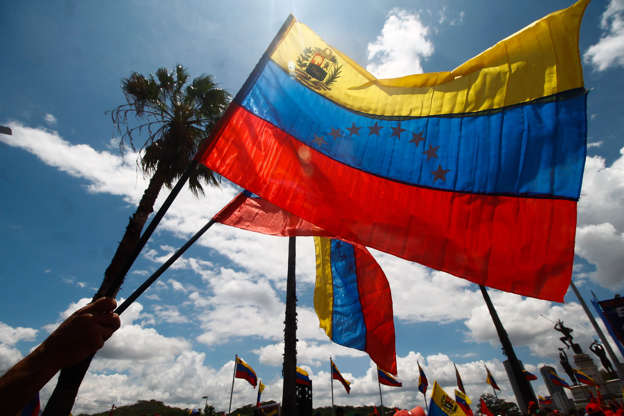 A man holds a flag of Venezuela in a demonstration to celebrate the 11th anniversary of the youth of the United Party of Venezuela, in Caracas on September 12. (Photo by Javier Campos/NurPhoto via Getty Images)