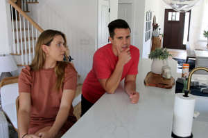 a man and a woman sitting at a table: Lauren Durfee and her fiance Sal Corso are shown in their new Eatontown home Thursday, August 12, 2021. The couple wanted to move from New York City to Monmouth County during the pandemic, but it wasn't that simple for the first-time homebuyers. They lost out bidding on two houses. And they waited for their new townhouse to be completed.