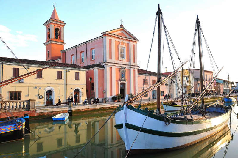 a boat is docked next to a building: Cesenatico. Photograph: Getty Images