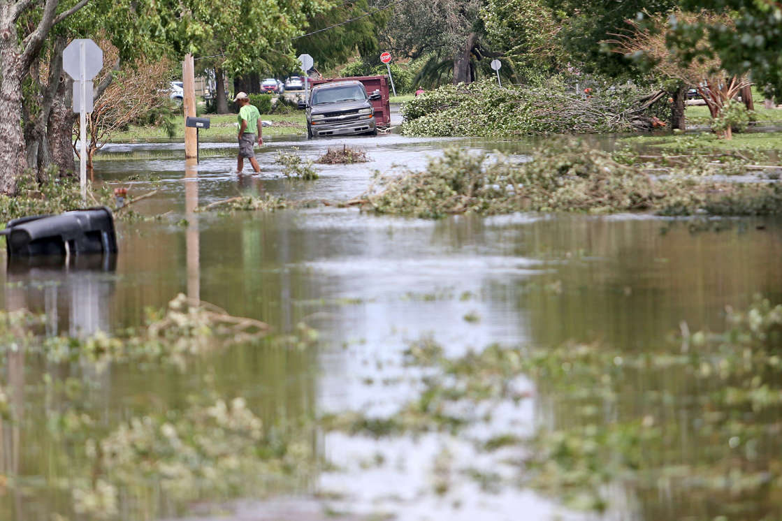 a close up of a pond: A man walks through the flooded streets in the Lakeview neighborhood of New Orleans in the aftermath of Hurricane Ida on Monday, August 30, 2021.