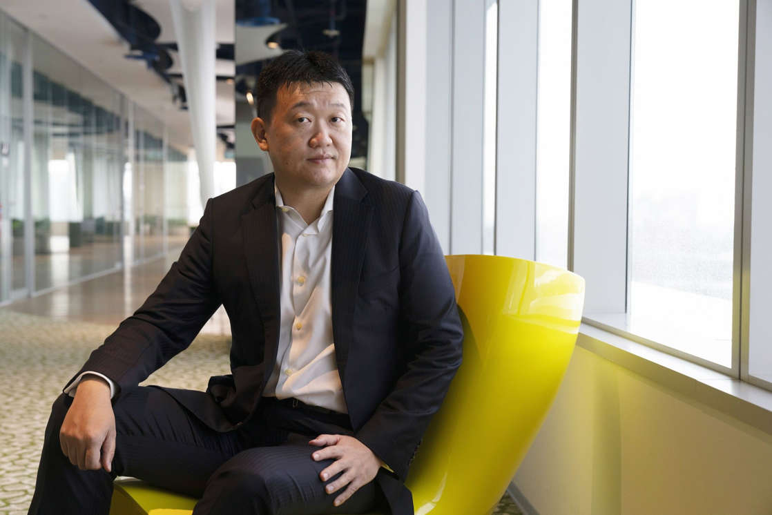 a man in a suit standing in front of a building: Sea Ltd. Chief Executive Officer Forrest Li
