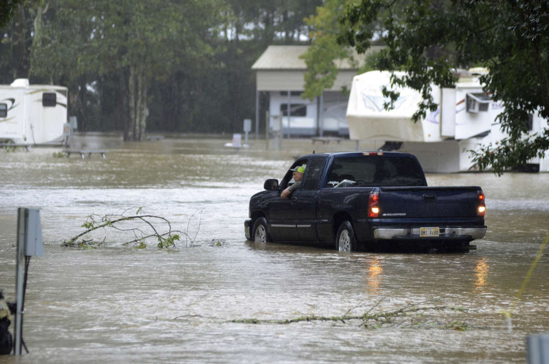 a car parked on the side of a river: A man inspects his RV in rising floodwaters in the aftermath of Hurricane Ida, as he drives through a campground in Magnolia, Miss., on Monday, Aug. 30, 2021.
