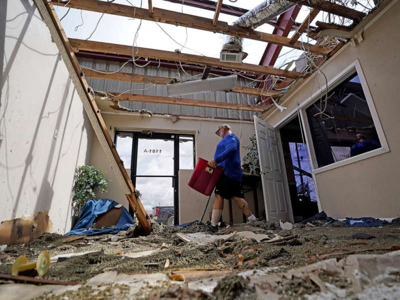 a person standing in front of a building: Rene Hebert cleans out the family's destroyed offices as cleans up in the aftermath of Hurricane Ida, Aug. 30, 2021, in Houma, La.