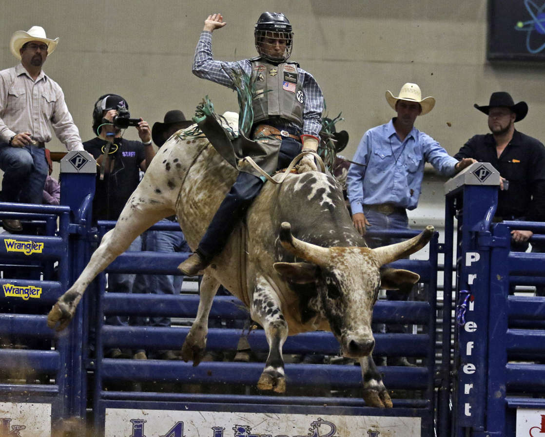a group of sheep standing on top of a building: In this Saturday, June 8, 2019, photo, Amadeu Campos Silva rides a bull named War Horse during the Caveman Invitational PBR at Ector County Coliseum in Odessa, Texas.