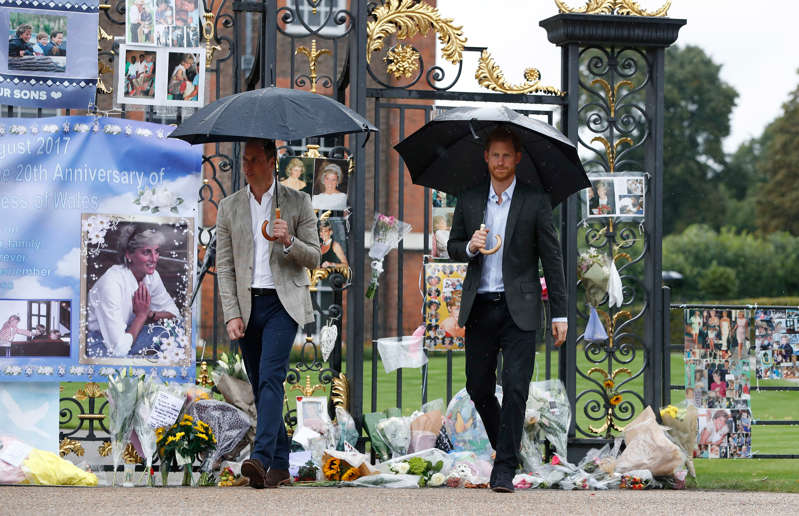 Prince Harry et al. standing in front of a crowd posing for the camera: William and Harry visiting tributes at the Golden Gates in 2017 on the 20th anniversary of their mother's death (Kirsty Wigglesworth/PA) (PA Archive)