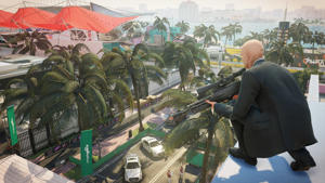 Agent 47 crouching with a sinper rifle on a roof overlooking the Miami race track in Hitman 2