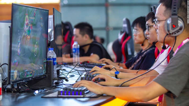 a group of people sitting at a table using a laptop computer: People playing online games one day before the China Digital Entertainment Expo & Conference at the Shanghai New International Expo Center on Aug. 1, 2019.
