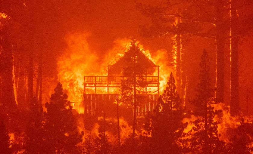 a close up of smoke: Flames consume multiple homes as the Caldor fire pushes into South Lake Tahoe, Calif., on Monday. (Josh Edelson / AFP via Getty Images)