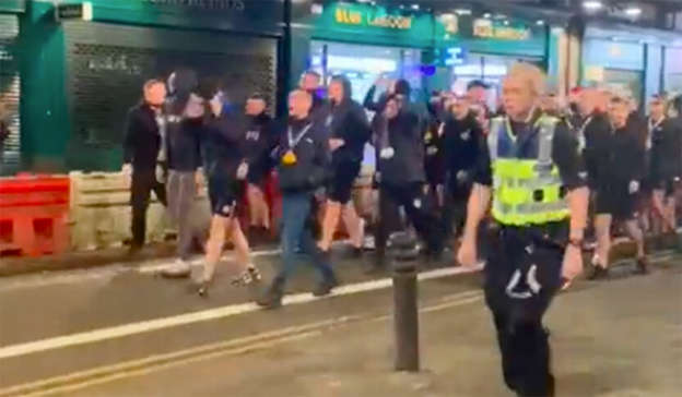 a group of people walking in front of a crowd: A group of Rangers fans were heard chanting the song. Pic: Twitter
