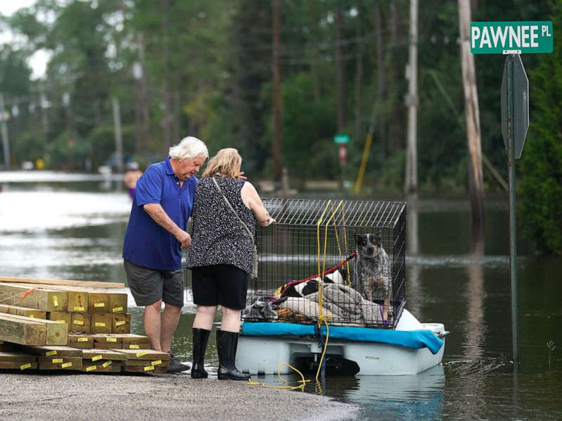 a person riding on the back of a boat in the water: A couple uses a paddle boat to transport their dogs through a flooded neighborhood on Aug. 30, 2021 in Kiln, Miss.