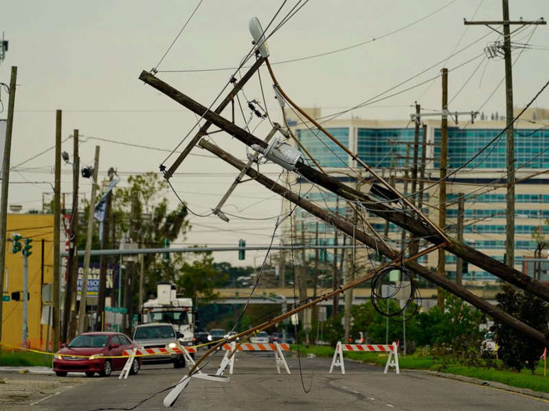 Vehicles are diverted around utility poles damaged by the effects of Hurricane Ida, Tuesday, Aug. 31, 2021, in New Orleans. New Orleans is without power, which may last for several weeks.