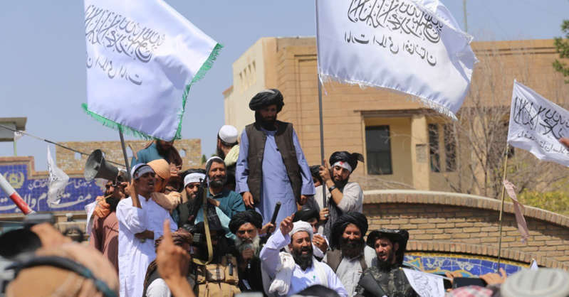 a group of people standing in front of a crowd: Taliban members gather and make speeches in front of Herat governorate after the completion of the U.S. withdrawal from Afghanistan, in Herat, Afghanistan on August 31, 2021.