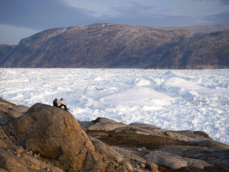 a man standing on a rocky hill: New York University student researchers sit on top of a rock overlooking the Helheim glacier in Greenland on Aug. 16, 2019, photo, Scientists have suggested there are multiple mysterious structures hidden beneath the Greenland ice sheet.