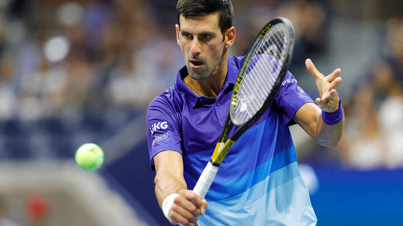 a close up of Novak Djokovic hitting a ball with a racket: Novak Djokovic is through to the second round of the US Open.