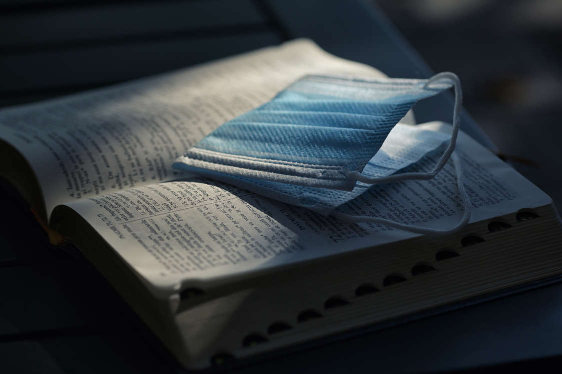 a book sitting on top of a bed: Grace Community Church will be paid $800,000 by Los Angeles County and the state of California after reaching a legal settlement to a lawsuit over COVID-19 restrictions in churches. This undated file photo shows a face mask sitting atop pages of a Bible.