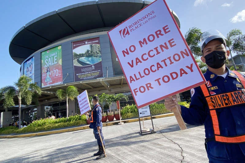 a person holding a sign posing for the camera: Security officers turn away people at a vaccination centre in Metro Manila's Las Pinas City, in the Philippines, on August 6. Whether the Delta variant prolongs the pandemic appreciably will depend on how long it takes to address the inequities in the production and distribution of vaccines globally. Photo: EPA-EFE