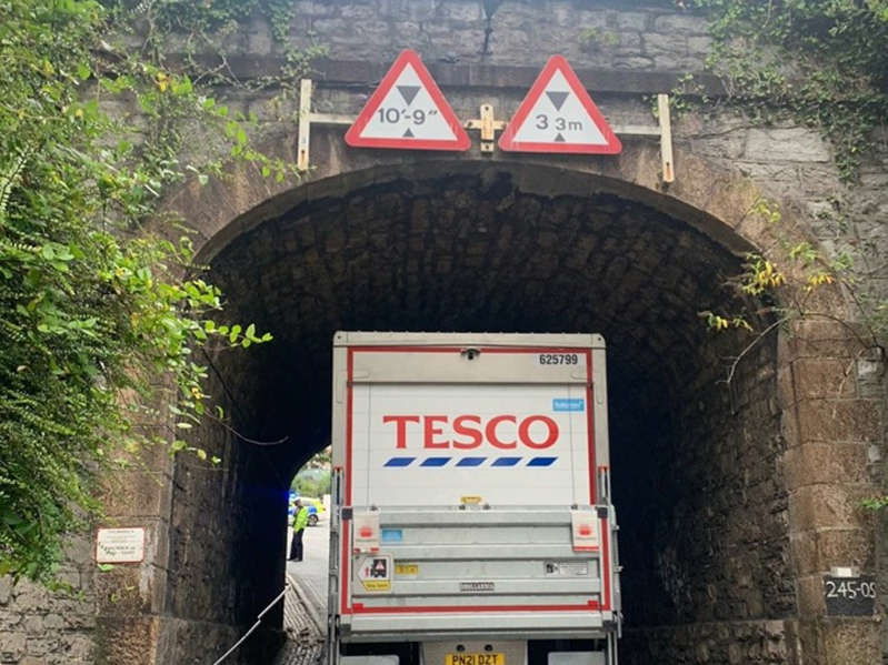 a sign on the side of a building: One strike: the refrigerated lorry that hit a bridge in Plymouth, blocking the main rail line in Devon and Cornwall - Network Rail