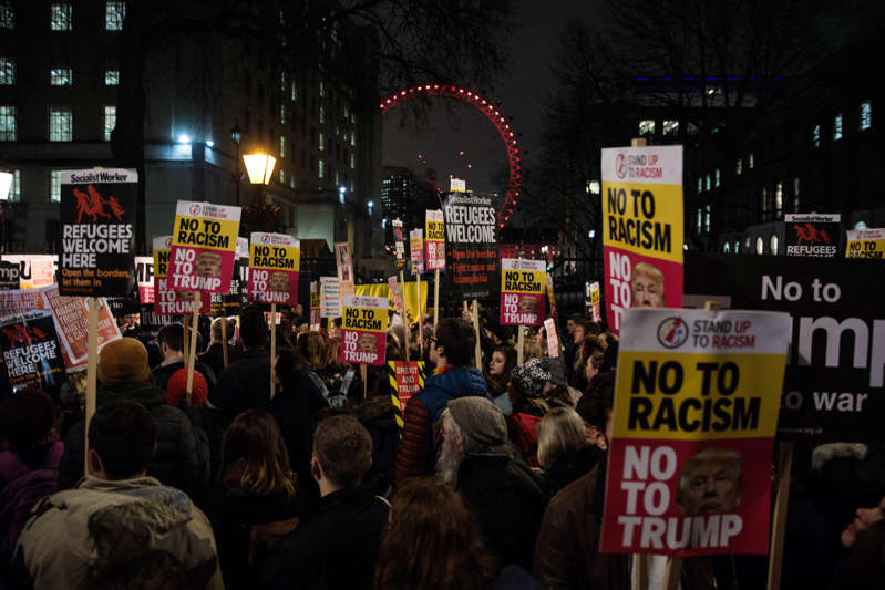a crowd of people standing in front of a store: Thousands of demonstrators hold up placards during a protest outside Downing Street against U.S. President Donald Trump's ban on travel from seven Muslim countries on January 30, 2017 in London, England. Jack Taylor/Getty