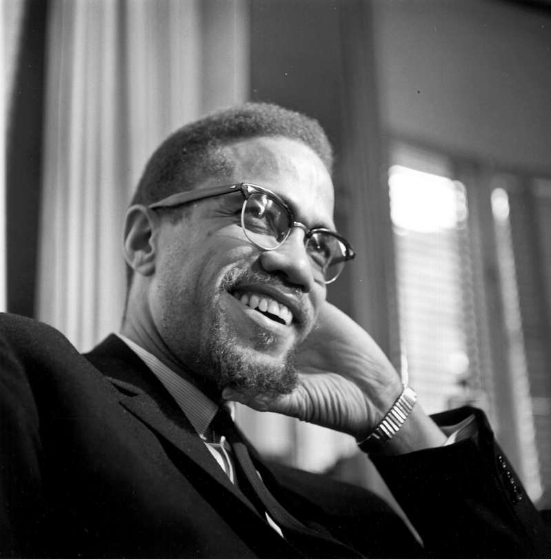 a man wearing glasses talking on a cell phone: Former Nation Of Islam leader and civil rights activist El-Hajj Malik El-Shabazz (aka Malcolm X and Malcolm Little) poses for a portrait on February 16, 1965, in Rochester, New York. Michael Ochs Archives/Getty