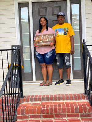 a man standing in front of a brick building: Nikki and John Daniel became first-time homebuyers in McCalla, Alabama, in August after realizing that their mortgage payments would be less than their monthly rent.