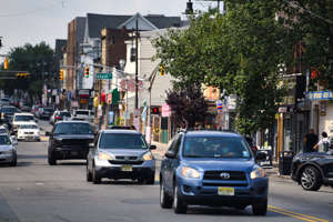 a car driving on a city street filled with lots of traffic: Main Street in South Paterson.