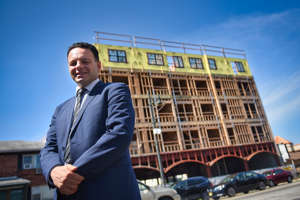 a man wearing a suit and tie standing in front of a building: Paterson Mayor Andre Sayegh standing in front of the retail and residential mixed development that is under construction along Main Street in South Paterson.