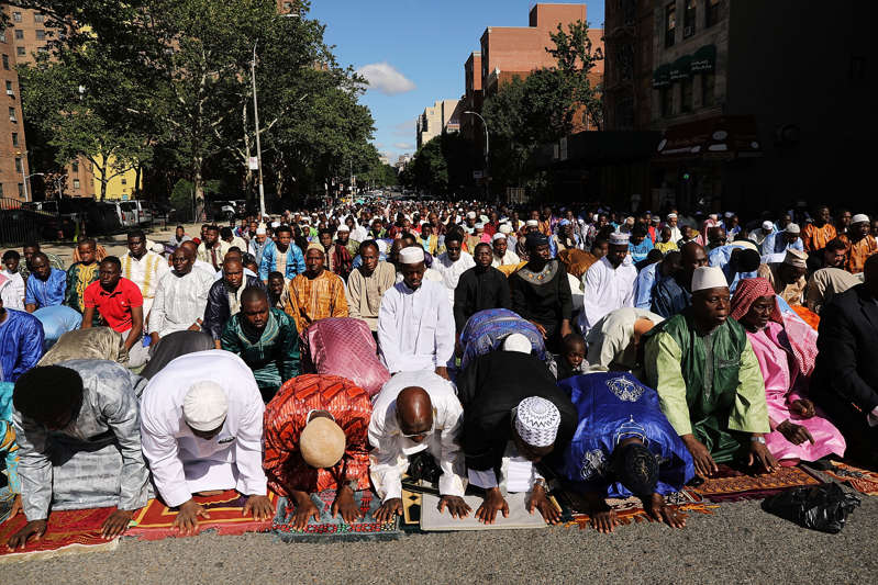 a group of people standing in front of a crowd: Muslims participate in an outdoor prayer event at Masjid Aqsa-Salam mosque, Manhattan's oldest West African mosque, to mark the end of Ramadan on June 15, 2018 in New York City. Spencer Platt/Getty