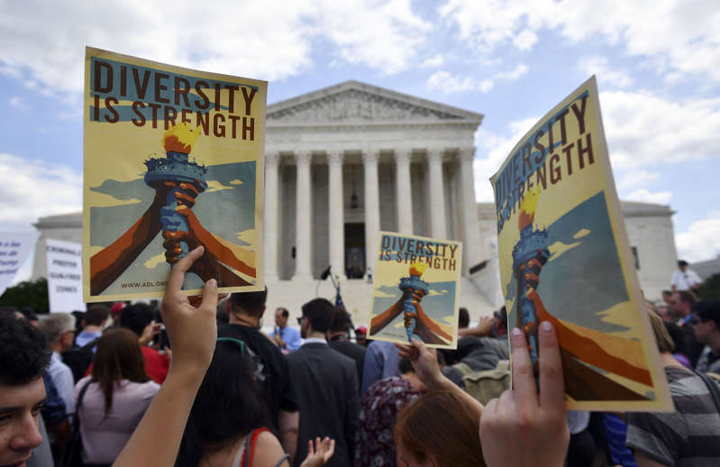 a group of people standing in front of a sign: People protest the Muslim travel ban outside of the US Supreme Court in Washington, DC on June 26, 2018. Mandel Ngan/AFP/Getty