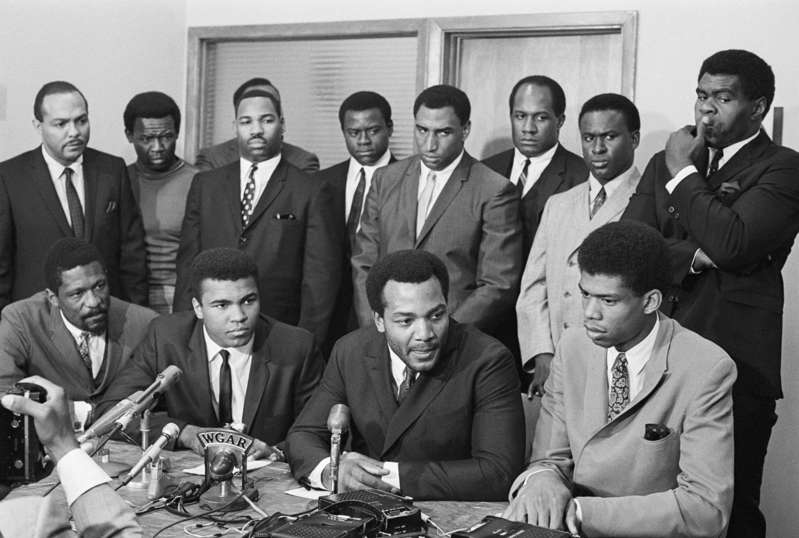 Carl Stokes, Bill Russell, Muhammad Ali, Bobby Mitchell, Jim Brown, Curtis McClinton, Willie Davis, John Wooten posing for a photo: Nation's top Negro athletes gathered for a meeting at the Negro Industrial and Economic Union to hear Cassius Clay's view for rejecting Army induction. Bettmann/Getty
