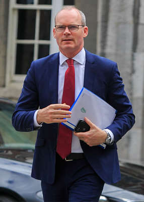 Simon Coveney wearing a suit and tie talking on a cell phone: Pic: Gareth Chaney/Collins Photos