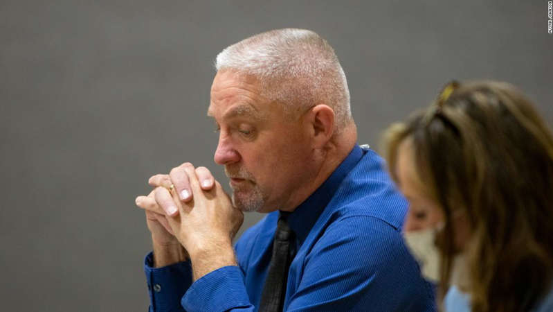 a man talking on a cell phone: Superintendent Kevin Purnell takes part in the Adrian School Board meeting on August 30.