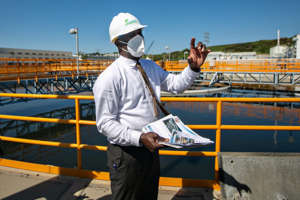 a man standing on a boat: Timeyin Dafeta, executive manager of the Hyperion Water Reclamation Plant, speaks to reporters recently during a tour of the plant. (Jason Armond / Los Angeles Times)