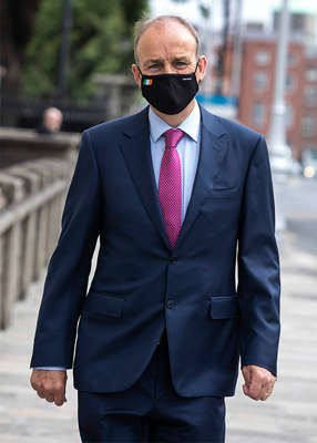 a man wearing a suit and tie talking on a cell phone: The Merrion Hotel scandal was also described as a 'major mess' by another TD, who maintained that the Taoiseach should have 'reprimanded' Mr Varadkar for attending the event. Pic: Damien Eagers/PA Wire