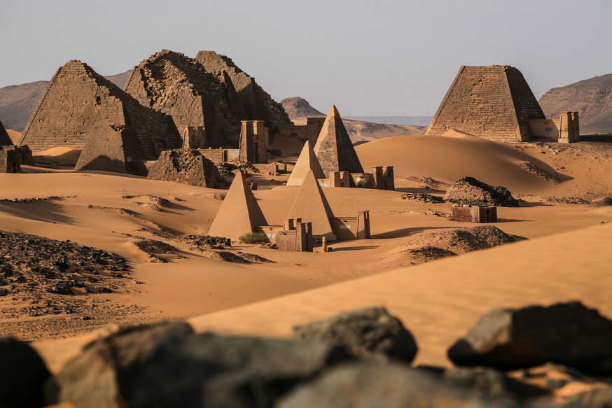 a view of a large rock with Hoggar Mountains in the background: The pyramids of Meroe, Sudan (Shutterstock)