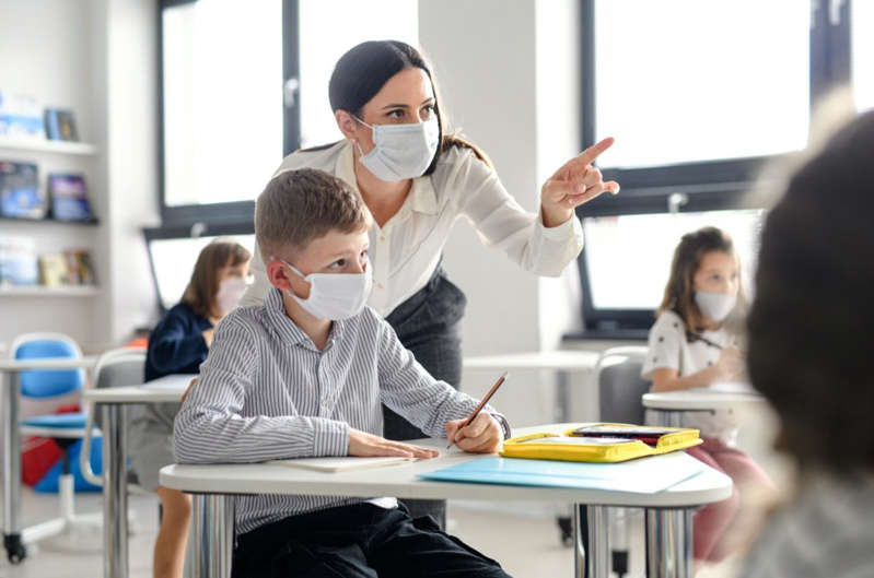 a person sitting at a table: Teacher and children with face mask back at school after covid-19 quarantine and lockdown.