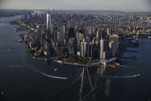 a large body of water with a city in the background: New York City As Covid Restrictions Are Lifted After Reaching Vaccine Goal