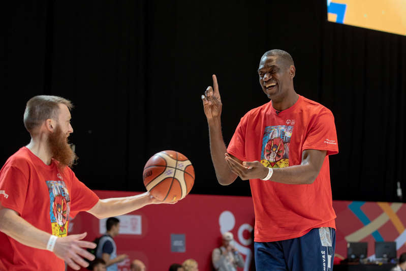 Dikembe Mutombo standing in front of a crowd: Dikembe Mutombo at the Special Olympics World Games in Abu Dhabi in 2019.