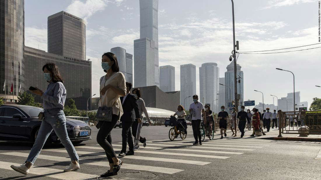 a group of people walking on a city street: Pedestrians wearing protective masks walk across a road in the central business district in Beijing, China, on Thursday, May 27, 2021.