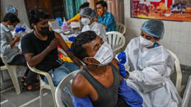 a group of people sitting at a table: Residents get inoculated with a dose of Covid-19 vaccine at a temporary vaccination centre in Mumbai on August 10. (AFP)